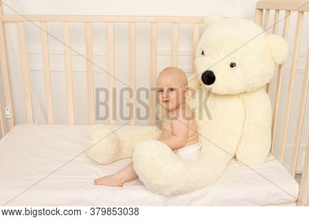 Baby Boy 8 Months Old Sitting In Diapers In A Crib With A Large Teddy Bear In The Nursery, Place For