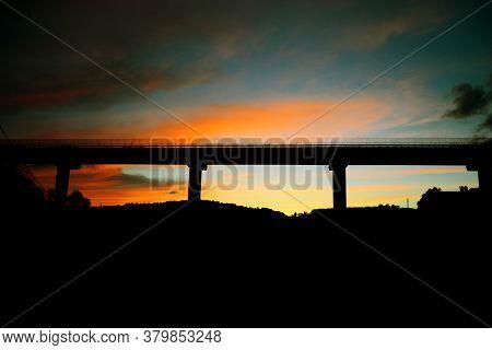 Pylon Bridge At Sunset. Paved Bridge At Sunset With Orange Clouds.