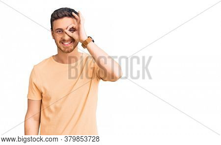 Handsome young man with bear wearing casual yellow tshirt doing ok gesture with hand smiling, eye looking through fingers with happy face.