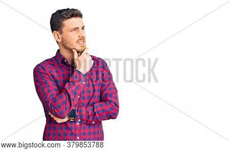 Handsome young man with bear wearing casual shirt thinking worried about a question, concerned and nervous with hand on chin