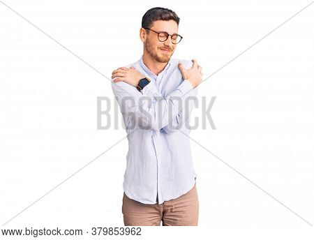 Handsome young man with bear wearing elegant business shirt and glasses hugging oneself happy and positive, smiling confident. self love and self care