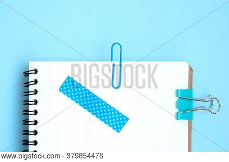 White Open Notebook With Blue Paper Clip, Clip And Piece Of Scotch Tape On Blue Background. Blue Set
