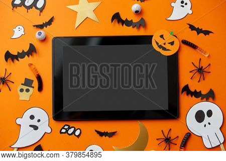 holidays and technology concept - tablet pc computer with halloween party props and decorations
