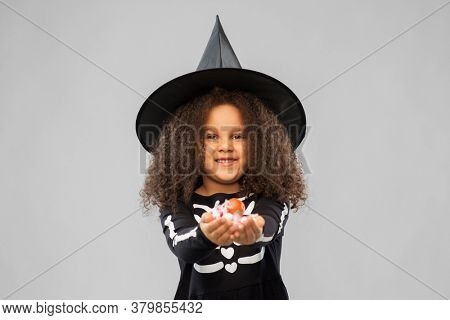 halloween, holiday and childhood concept - smiling african american girl in black costume and witch hat with candies trick-or-treating over grey background