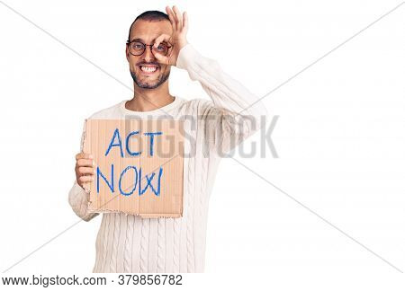 Young handsome man holding act now banner smiling happy doing ok sign with hand on eye looking through fingers