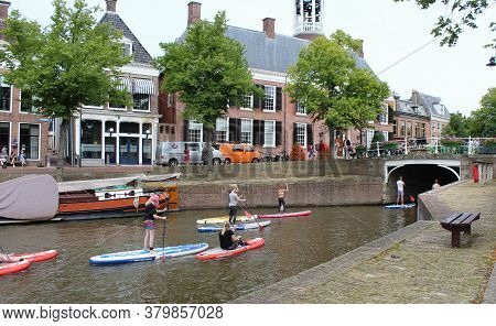 Dokkum, Netherlands, 22 July 2020: Tourists Exploring The Waterways Of Dokkum By Sup (stand Up Paddl