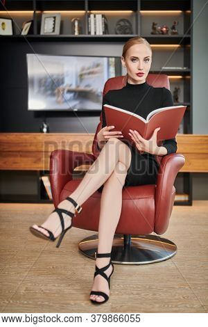 Portrait of a stunning fashionable woman sitting in a luxurious leather chair and reading a magazine. Business, elegant businesswoman. Modern interior, furniture.