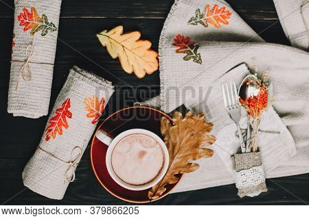 A Rustic Autumn Still Life With Linen Kitchen Towels, Textile Napkin And Coffee Cup On A Wooden Tabl