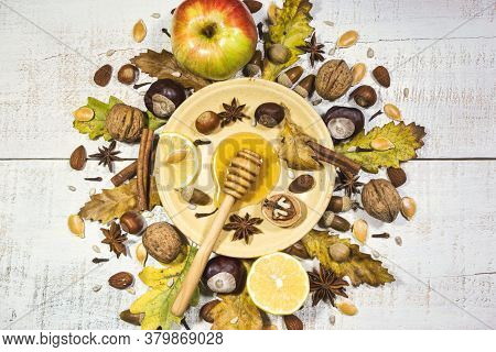 Autumn Composition With Nuts, Honey, Seeds, Spices, Acorns, Chestnuts, Fruits And Autumn Leaves. Top