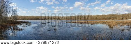 White Puffy Clouds Float In A Sunny Blue Sky Over The Rippling Waters Of A Virginia Marsh.