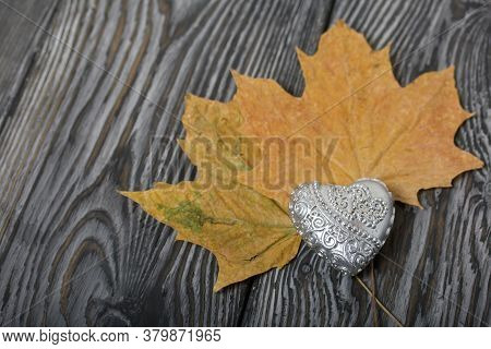 Decorative Candle In The Shape Of A Heart. Dried Maple Leaves. Love And Togetherness Objects. On Pai