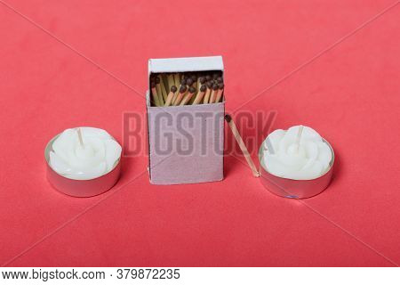 Two Decorative Candles In The Shape Of A Flower. Next To Them Is A Box Of Matches. On A Coral Backgr