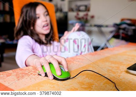 Focus - Computer Mouse, Hand. The Child Is Sitting On A Chair, Studying At The Computer. Discontent.