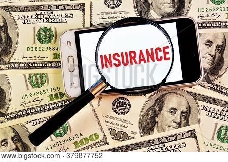Insurance-text Inscription In The Smartphone On The Background Of The Money Collection. Ensuring Fin