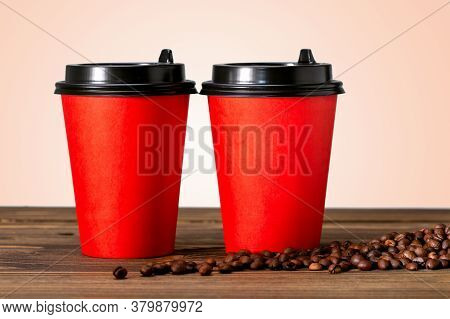 Two Paper Cup Of Coffee And Coffee Beans On Wooden Table. Coffee To Go Concept.