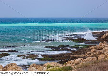 Amazing Turquoise Waves And White Foam. Waves Crashing On The Rocky Coast Of Lebanon. Blue Sea Water