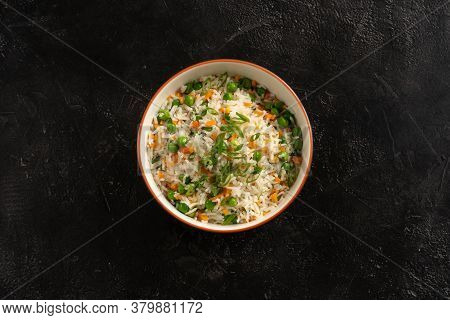 Asian garnish, boiled rice with vegetables, peas, carrots and green onions in a round plate on a bla