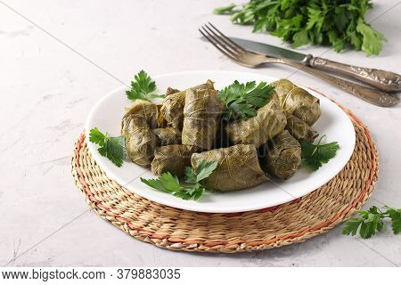 Dolma - Stuffed Grape Leaves With Rice And Meat On A White Plate On Light Gray Background. Tradition