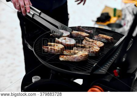 Man Grilling Delicious Fish On A Portable Bbq,