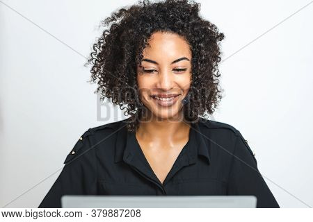 Beautiful Black Afro Young Woman With Headset In Front Of A Laptop Smiling. Customer Service