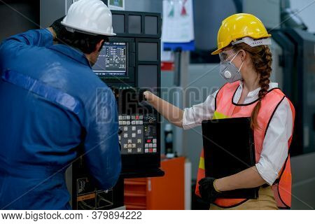 Factory Worker Woman With Mask Point To The Monitor Of Machine With Engineer Man Also Discuss Togeth