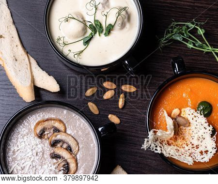 Mushroom Cream Soup In A Black Plate With Croutons Of White Bread. Cream Of Champignon Soup With Cra