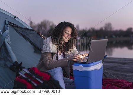 Female Freelancer Camping By The Lake, Sitting On The Tent Entrance And Working On A Laptop Computer
