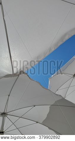 Triangle Shaped Parts Of Three White Sunshades On Clear Blue Sky Background With Copy Space. Sun Shi