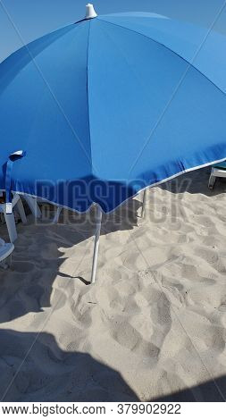 Blue Sunshade On Clear Beach Sand In Sunny Noon. Geometry Of Summer Beach. Sea Vacation Background W