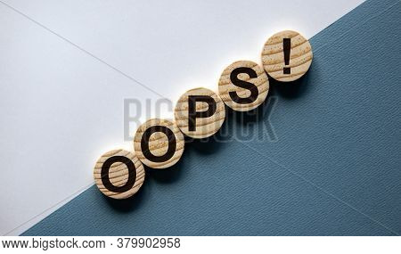 Wood Circles With Word 'oops' On Paper White And Blue Background, Copy Space. Business Concept.