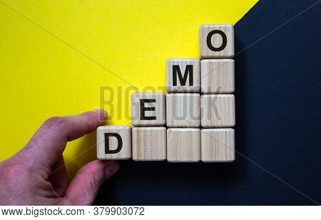 Wood Cubes With Word 'demo' Stacking As Step Stair On Paper Black And Yellow Background, Copy Space.