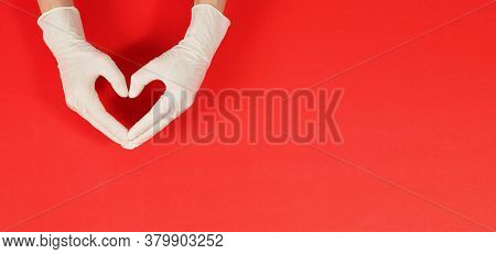 A Hand Is Doing Love Hand Sign And Wear White Surgical Gloves Or Latex Gloves On Red Background.