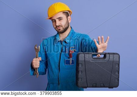 Young Unshaved Male With Wrench And Tool Case In Hands, Guy Wearing Helmet And Overalls, Looking Dir