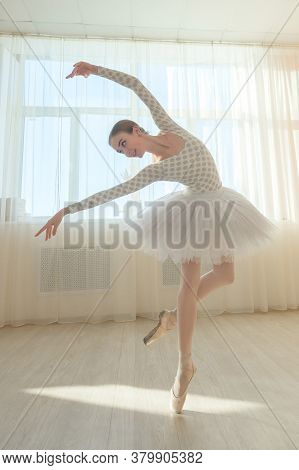 Beautiful Graceful Ballerina Is Practicing In The Hall Against The Background Of A Window. Slender W