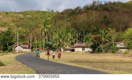 Lombok, Indonesia - October 11th 2017: A Family Walking Along The Road At A Village Near Mawun Beach
