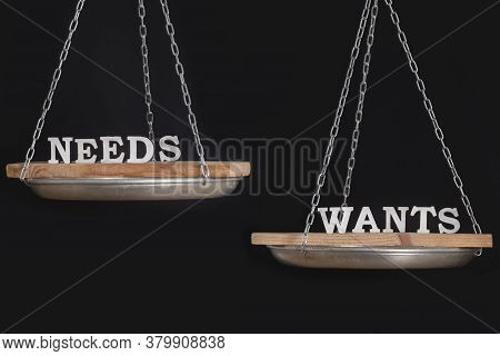 Words Wants And Needs In Balance. Scales On Black Background Close Up