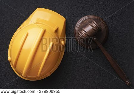 Construction Helmet And Judges Gavel On Black Background. Top View. Construction And Law