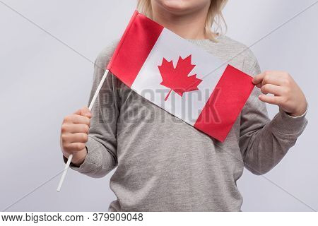 Child Holds Flag Of Canada. Close Up. Immigration To Canada. Education In Canada For Children