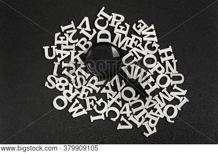 Magnifying Glass Surrounded By Letters Of Latin Alphabet On Black Background. Search Concept.