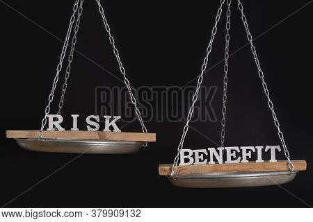 Words Risk And Benefit In Balance. Concept Of Equilibrium. Scales On Black Background.