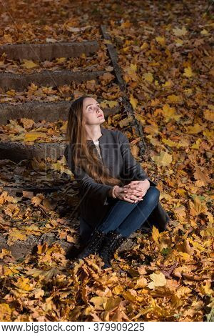 Young Woman Sits On Fallen Leaves In Autumn Park. Vertical Frame.