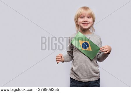 Surprised Child Holding Flag Of Brazil. Portrait Of Blond Boy With Brazil Flag On White Background