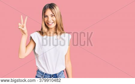 Beautiful caucasian woman with blonde hair wearing casual white tshirt showing and pointing up with fingers number two while smiling confident and happy.
