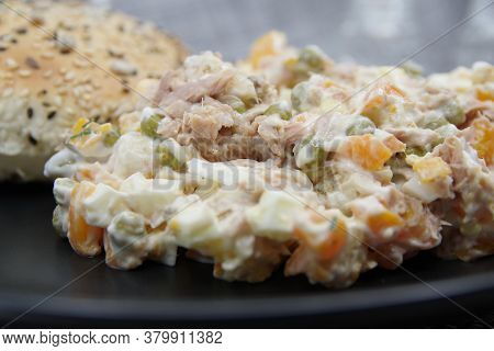 Tuna Salad In Black Plate. Ingredients: Tuna, Carrots, Eggs, Onion, Canned Peas, Croutons, Mayonnais