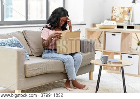 delivery, shipping and people concept - young african american woman opening parcel box at home and feeling disappointed with wrong order