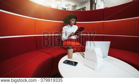 An Exquisite Black Woman Entrepreneur Sitting On A Curved Red Sofa Indoor Of A Modern Office Coworki