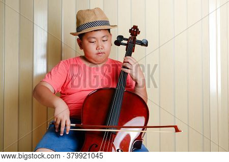 Asian Boy Playing A Classical Instrument Cello At His House