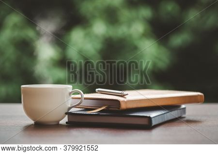 Hot Coffee, Smoke, With Books And Pens For Note Taking With Beautiful Nature Background.