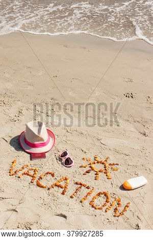 Inscription Vacation Made Of Amber Stones, Accessoriess For Sunbathing And Passport On Sand At Beach