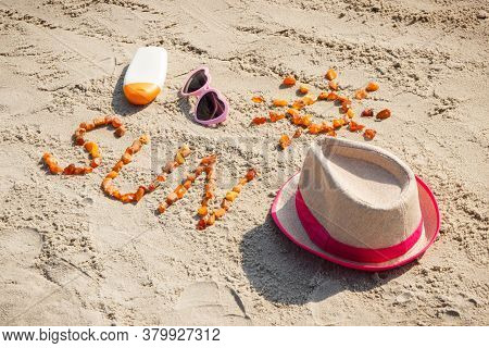 Inscription And Shape Of Sun Made Of Amber Stones, Sunglasses, Sun Lotion And Straw Hat On Sand At B